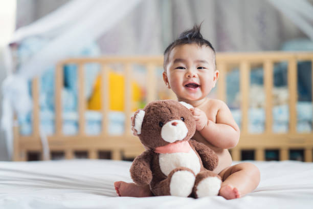 asian baby sit with teddy bear - babies stock photos and pictures