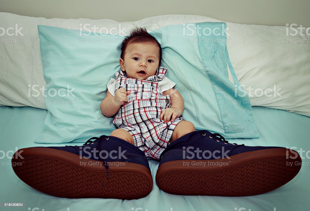 Asian Baby Wearing Big Shoes on The Bed stock photo