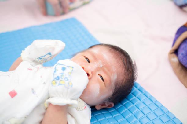 Bebê asiático com pó no rosto - foto de acervo