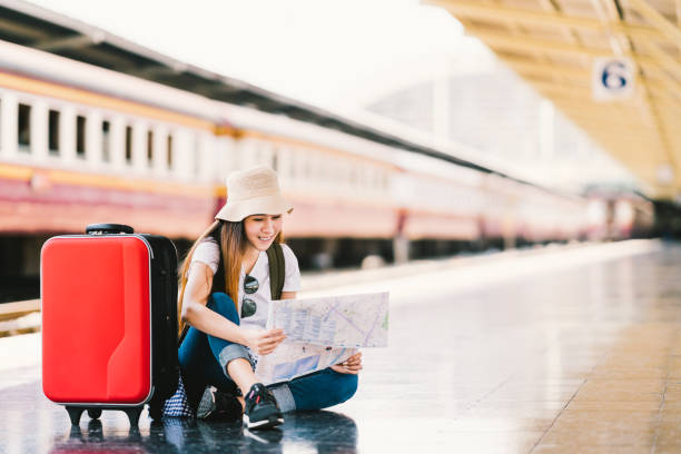 asian backpack traveler woman using generic local map, siting alone at train station platform with luggage. summer holiday travelling or young tourist concept - donna valigia solitudine foto e immagini stock
