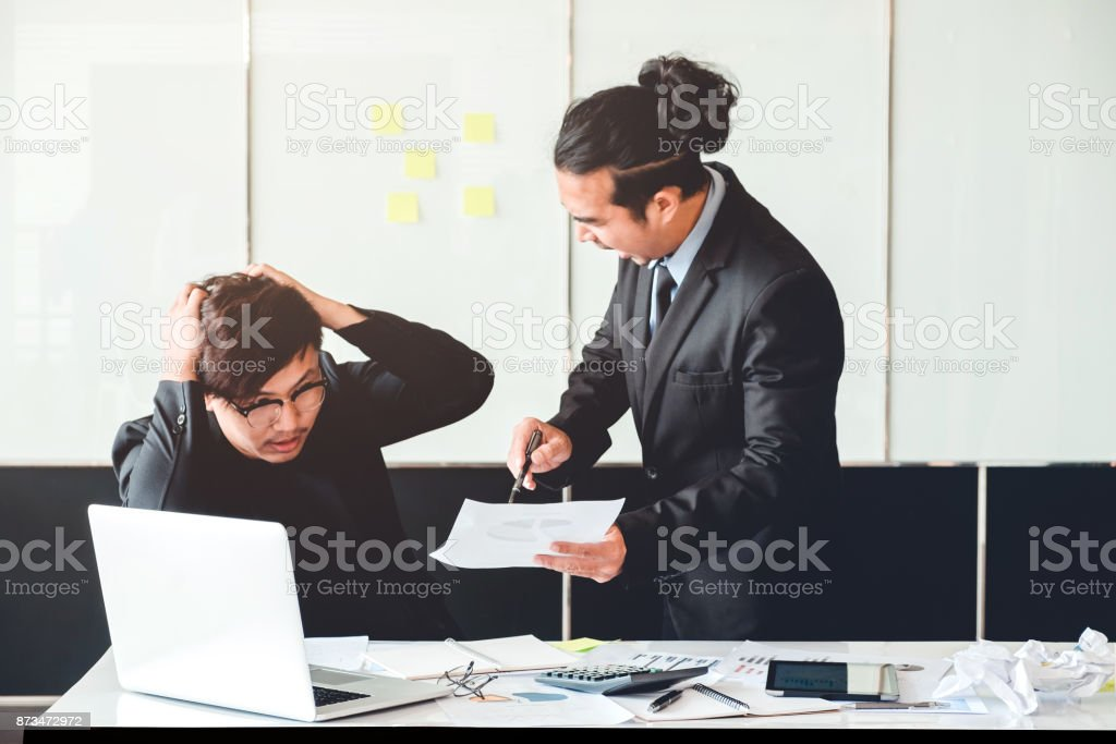 Asian Bad angry boss yelling at business man sad depressed employee reprimand from team leader missed deadline concept stock photo