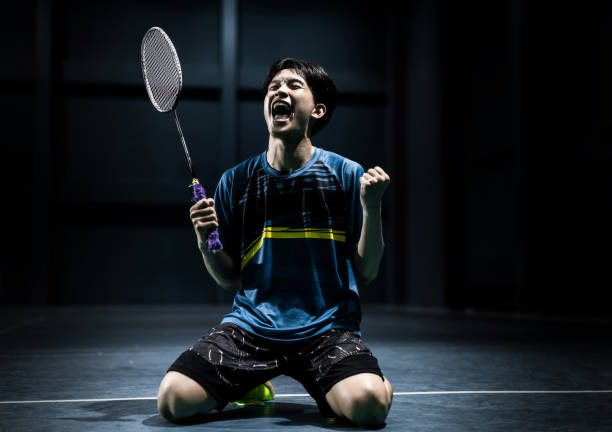 Asian badminton player is glad that he wins competition Asian badminton player is glad that he wins competition badminton stock pictures, royalty-free photos & images