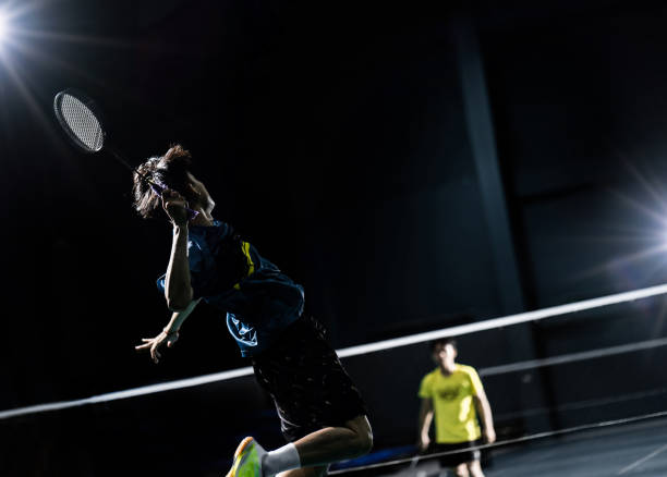 Asian badminton player is hitting in court Asian badminton player is hitting in court badminton stock pictures, royalty-free photos & images