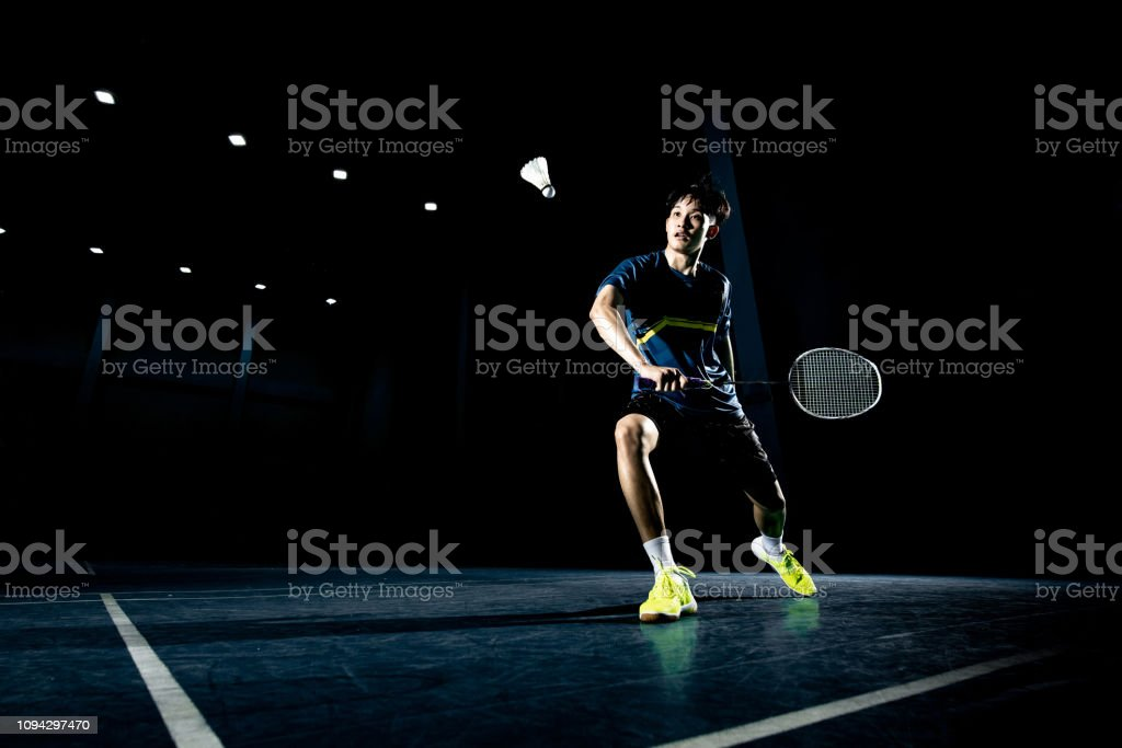 Cтоковое фото Asian badminton player is hitting in court