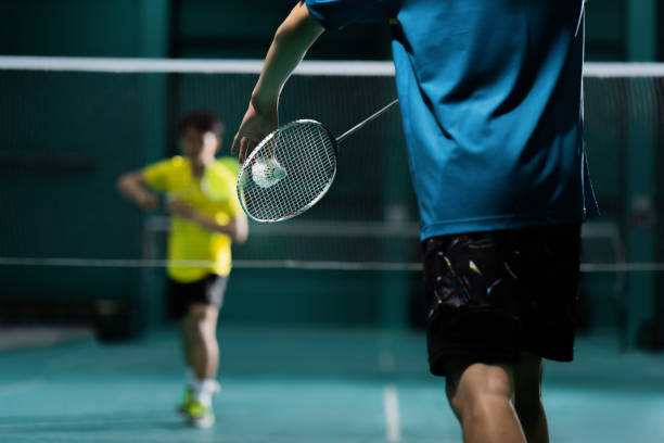 Asian badminton player is hitting in court stock photo