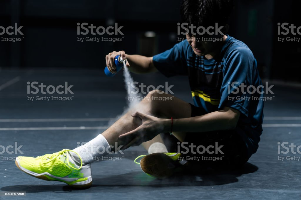 Cтоковое фото Asian badminton player is injured in the leg, he is cramping and using a spray