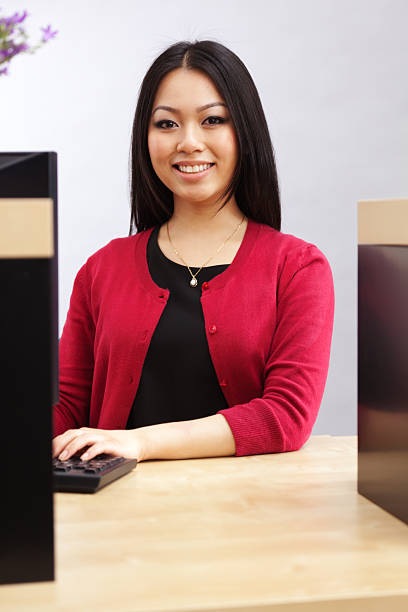 Asian Bank Teller at Banking Counter, Financial Advisor Providing Service stock photo