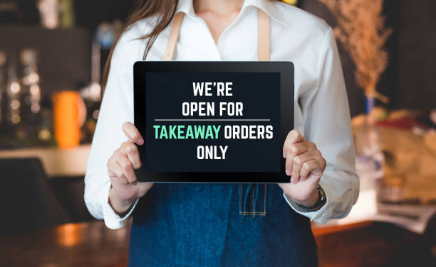 asian barista holding tabblet sign we're open for takeaway orders only infront of counterbar.social distancing concept when coronavirus is outbreak in city stock photo