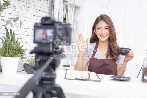 istock Asian barista looking to camera for live to social media. Female barista using social media to promote her shop. People with SME, Online Business, Startup Concept. 1006399258