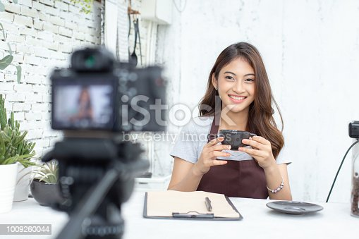 istock Asian barista looking to camera for live to social media. Female barista using social media to promote her shop. People with SME, Online Business, Startup Concept. 1009260044