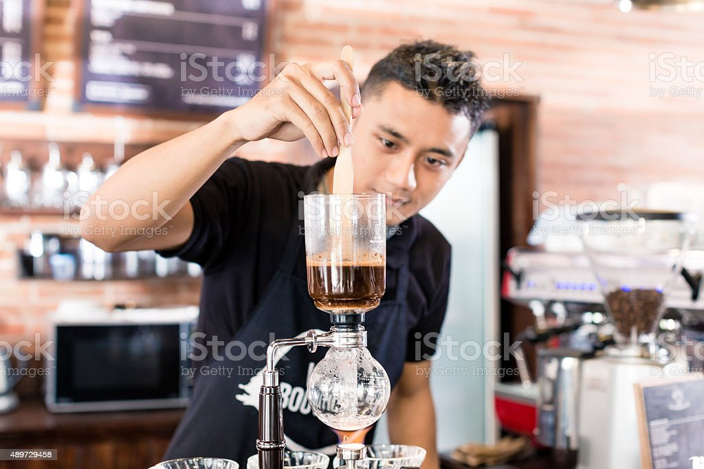 Asian Barista offering cup of drip brew coffee stock photo