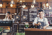 Asian Barista of Small business owner serving a cup of coffee to young customer at the coffee counter in coffee shop