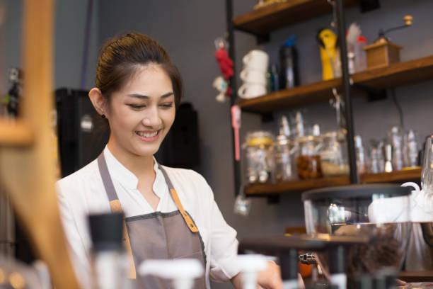 Asiatische Barista Frau Kaffeezubereitung mit Kaffeemaschine im Coffee Shop. Menschen mit Barista in Café-Konzept. – Foto