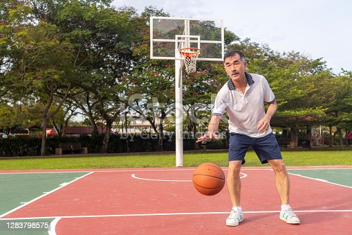 Senior basketball player is dribbling basketball on outdoor streetbasket court.