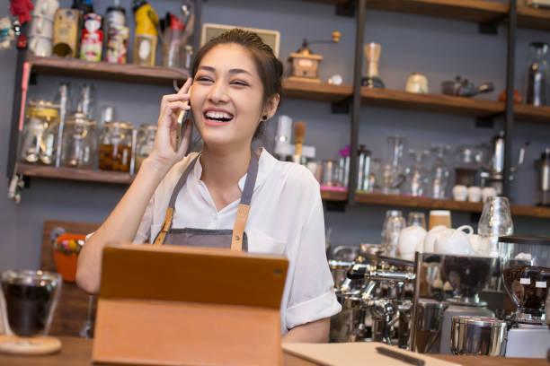 Asiatischen schöne Barista im Gespräch mit Kunden mit attraktiven Lächeln auf den Lippen. Frau mit Smartphone mit glücklich Emotion im Coffee Shop. – Foto