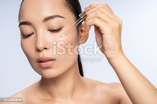 Close up of pretty lady putting anti-ageing moisturizing serum to under eye area. Beauty therapy concept