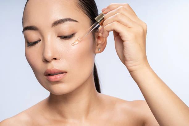 Asian beautiful female is applying eye serum stock photo