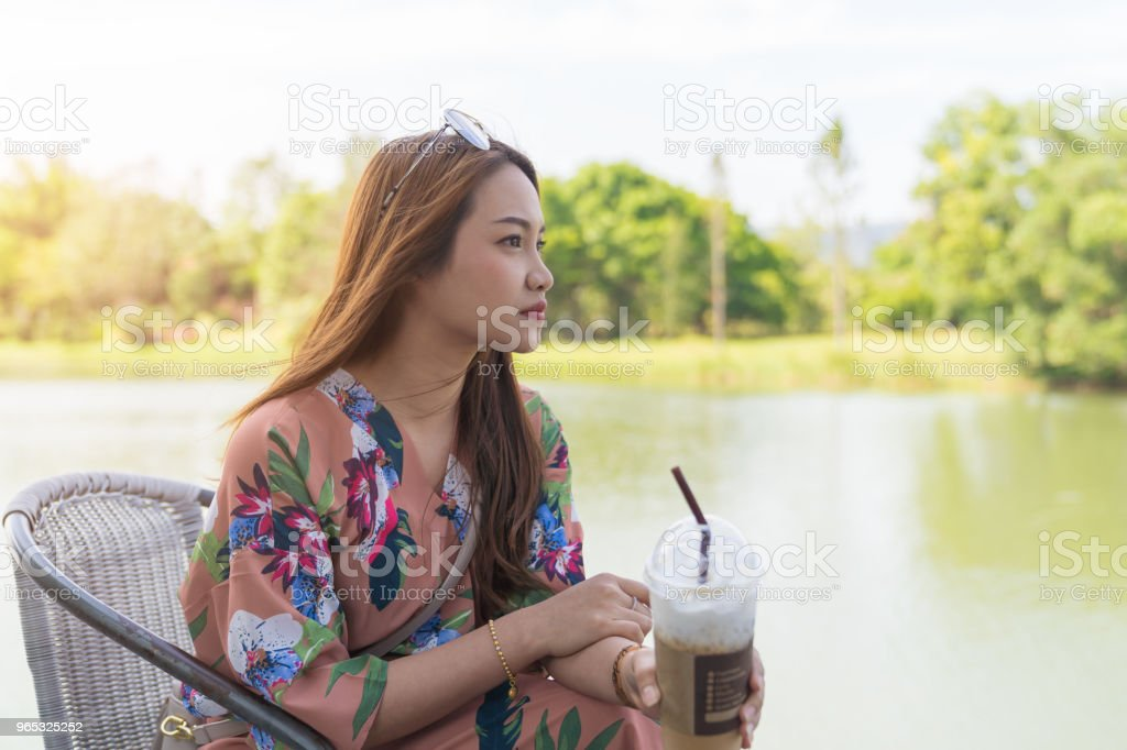 Asian beautiful woman enjoying drink coffee cold in pastic glass take home. zbiór zdjęć royalty-free