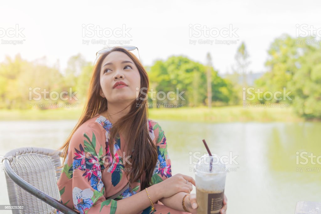 Asian beautiful woman enjoying drink coffee cold in pastic glass take home. zbiór zdjęć royalty-free