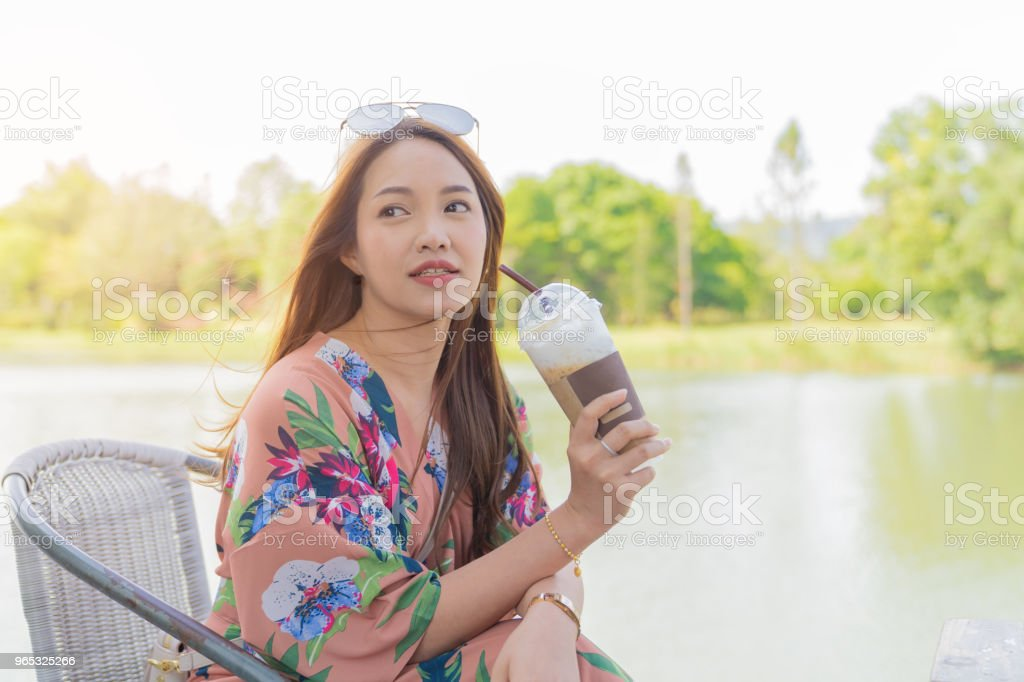Asian beautiful woman enjoying drink coffee cold in pastic glass take home. royalty-free stock photo