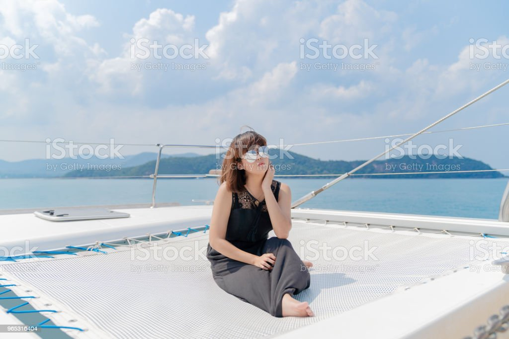 Asian beautiful woman portraits on luxury yacth in the sea and blue sky background. zbiór zdjęć royalty-free