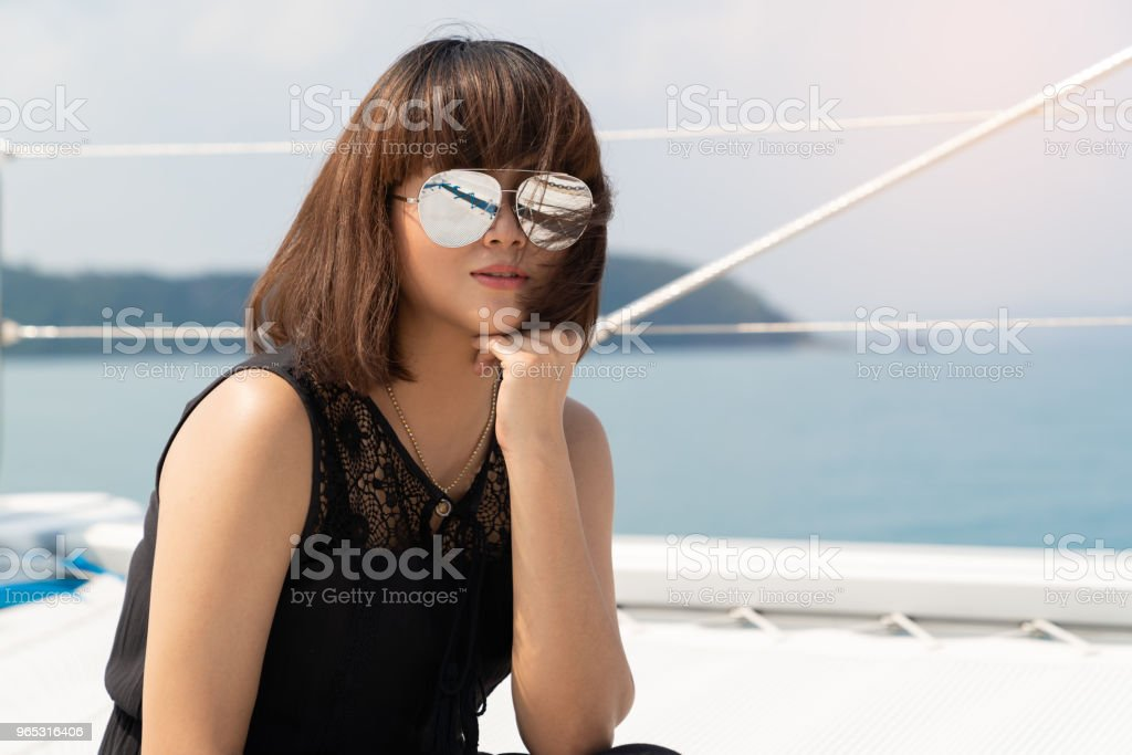 Asian beautiful woman portraits on luxury yacth in the sea and blue sky background. royalty-free stock photo