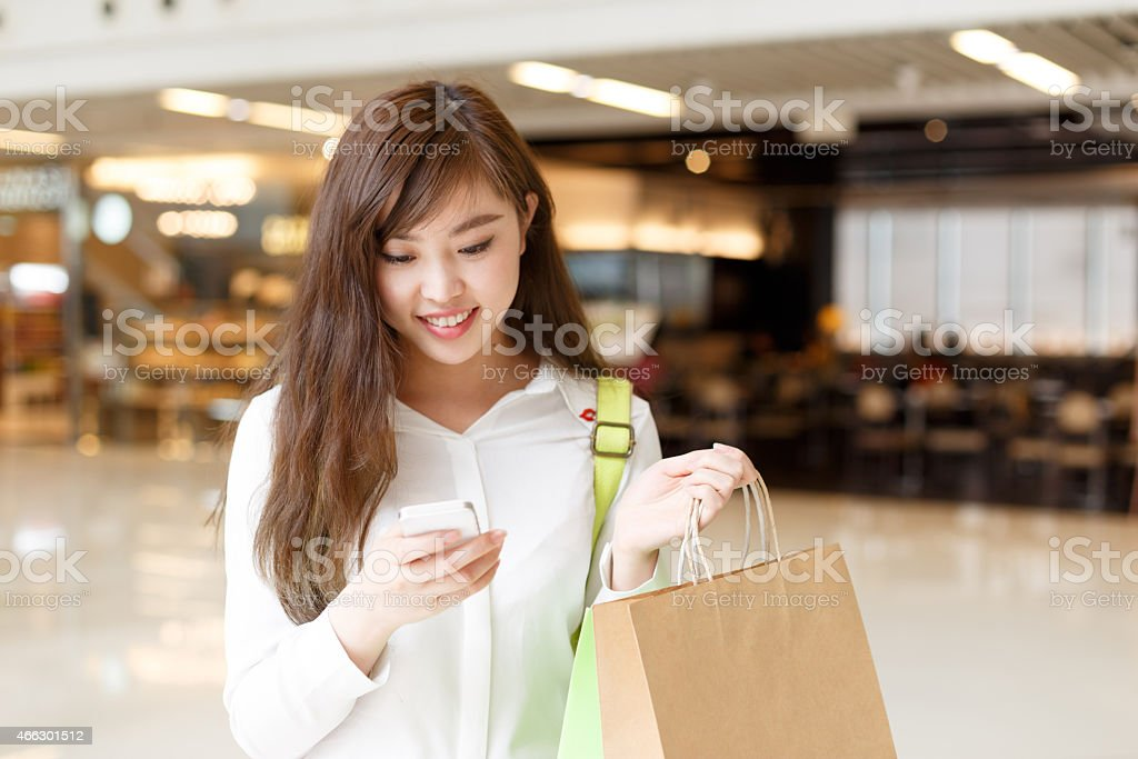 asian beautiful woman shopping and using smart phone indoor stock photo