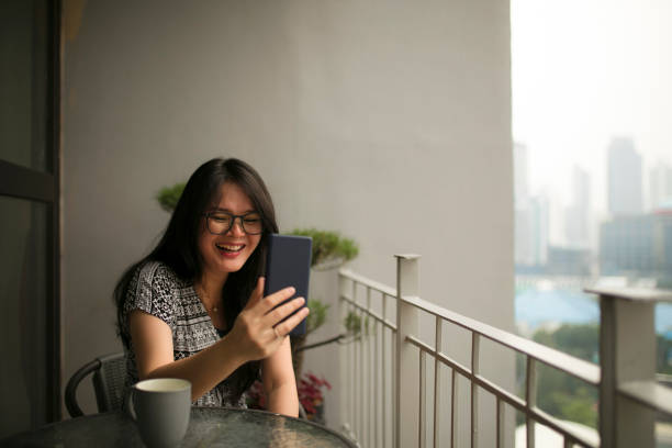 asian beautiful woman video calling her loved one using phone  in her apartment stock photo