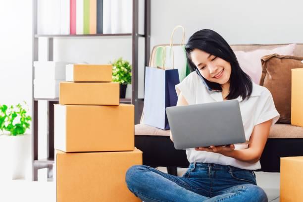 wanita cantik asia bekerja dengan laptop dan smartphone ke toko bisnis online di rumah. pemilik pengusaha wanita memulai dengan menerima pesanan, memeriksa produk, bersiap untuk mengirimkan produk kepada pelanggan. - bisnis online potret stok, foto, & gambar bebas royalti
