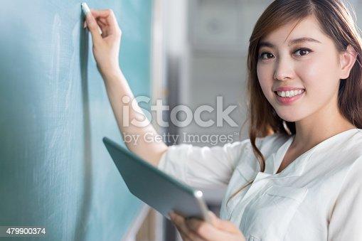 485539628 istock photo asian beautiful woman writing on blackboard with tablet 479900374