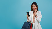 istock Asian beautiful women blogger are using smart phone shopping online with a shopping bag isolated in blue color background with copy space.Concept of online shopping business with Promotion and Sale. 1185418020