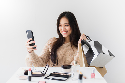 Asian beautiful women blogger are using the smartphone live streaming online with a shopping bag In the white room with cosmetics on table.Concept of online shopping business.