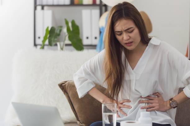aziatische mooie vrouwen voelen menstruele krampen en buikpijn na de menstruatie. hand holding maag en buik na het innemen van een medicijn. probleem en wanorde van vrouwelijk lichaam. - buikpijn stockfoto's en -beelden