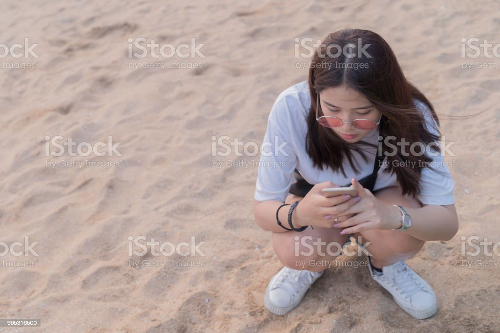Asian beautiful young teenager playing smart phone on the beach background. royalty-free stock photo
