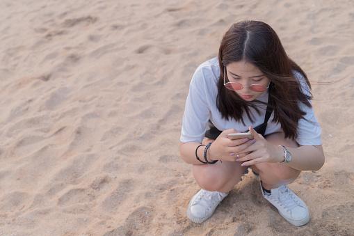 Asian Beautiful Young Teenager Playing Smart Phone On The Beach Background - zdjęcia stockowe i więcej obrazów Azja