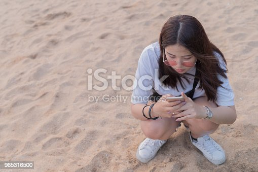 Asian Beautiful Young Teenager Playing Smart Phone On The Beach Background Stock Photo & More Pictures of Adult