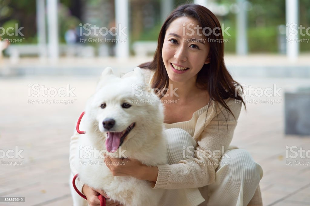 Asian beauty embracing her dog smiling at camera outdoor in garden stock photo