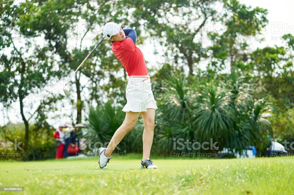Asian beauty swinging a golf club in course stock photo