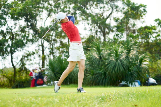 asian beauty swinging a golf club in course - female golfer stock photos and pictures