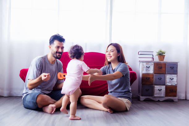 Asian beauty young mother calling her toddler daughter for coming to mom. Little girl walking to mother and father encouraging little daughter with smile face. Happy family. Mixed race family concept stock photo