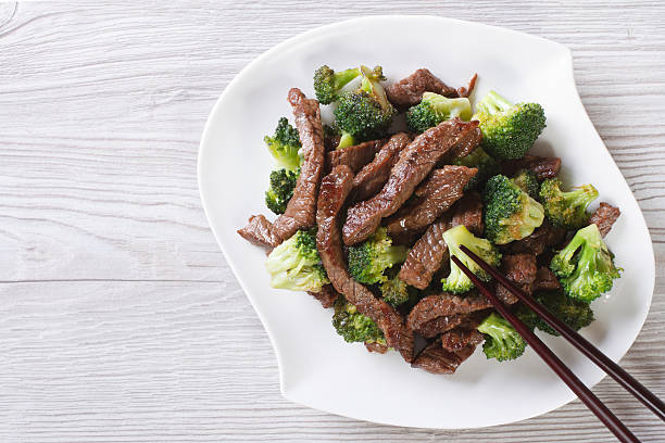 Asian beef with broccoli and chopsticks. horizontal top view stock photo
