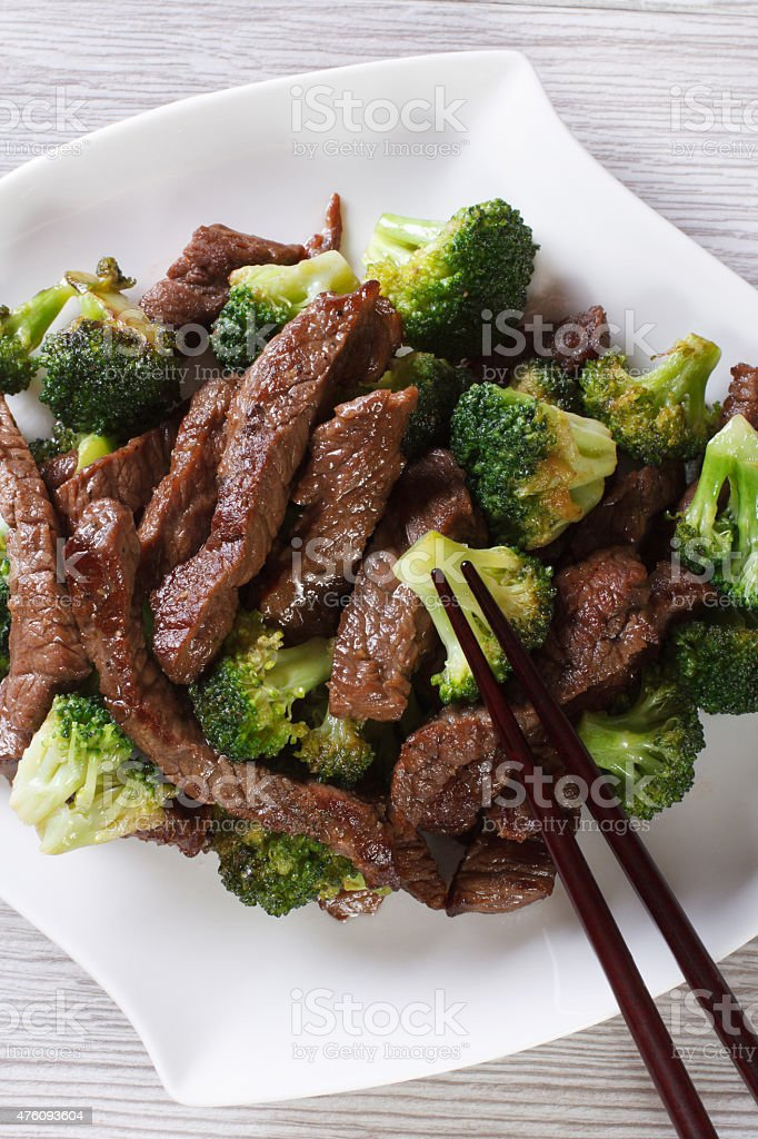 Asian beef with broccoli and chopsticks. vertical top view stock photo