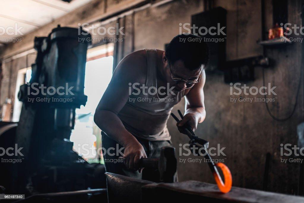Asiático ferreiro forjar metal em sua oficina - Foto de stock de 40-49 anos royalty-free