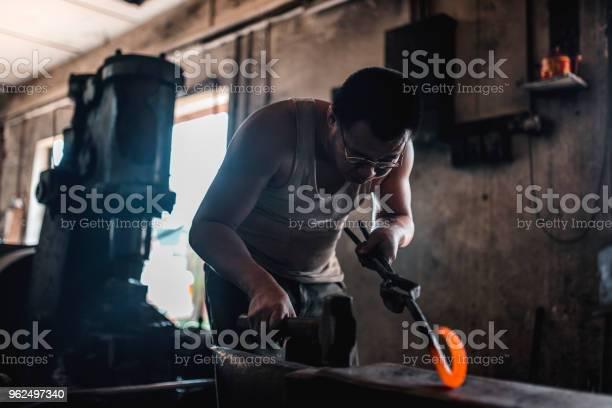 Foto de Asiático Ferreiro Forjar Metal Em Sua Oficina e mais fotos de stock de 40-49 anos