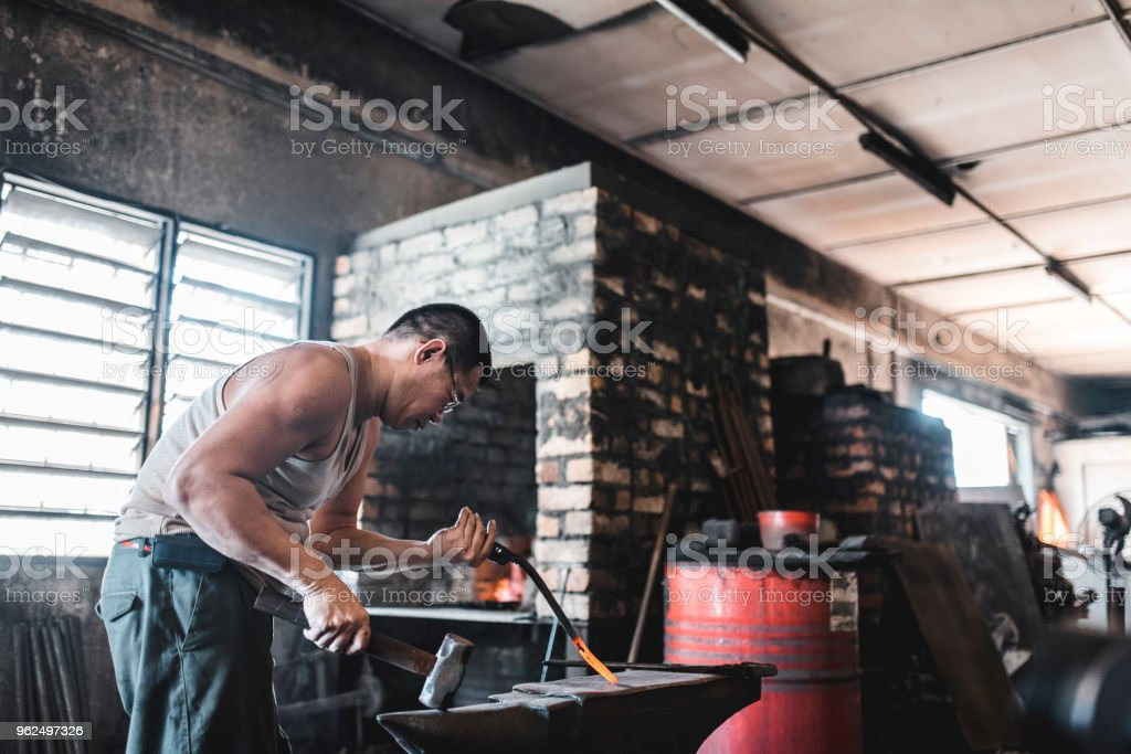 Asian blacksmith working in the forge - Royalty-free 40-49 Years Stock Photo