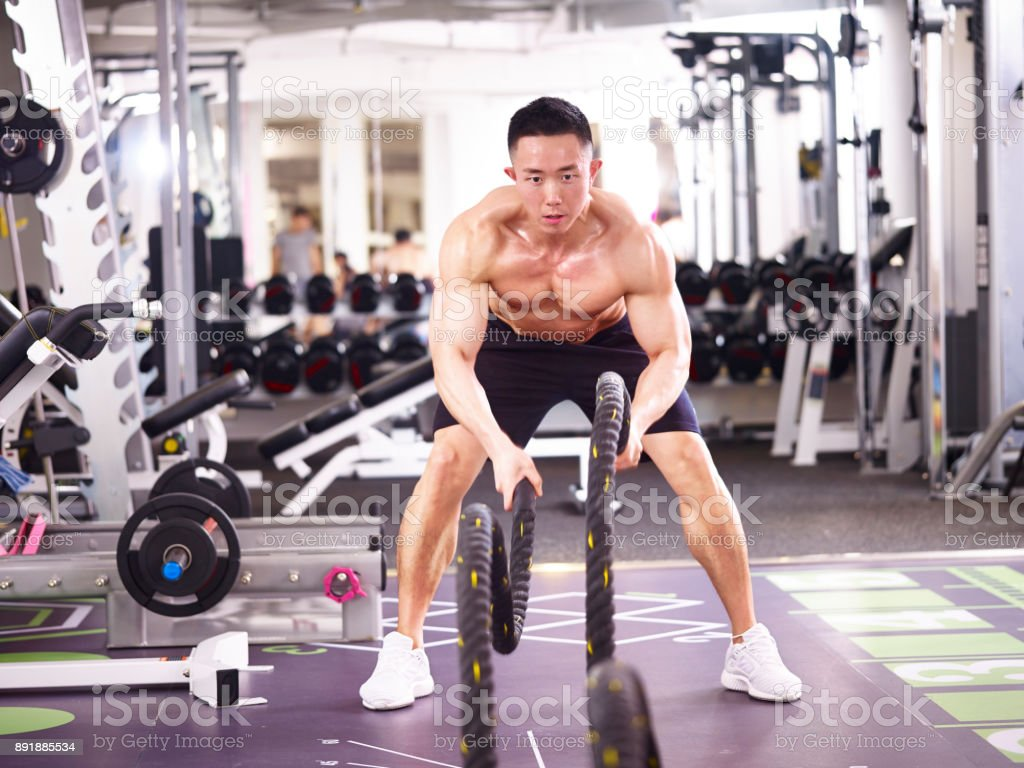 asian bodybuilder exercising in gym using battle ropes stock photo