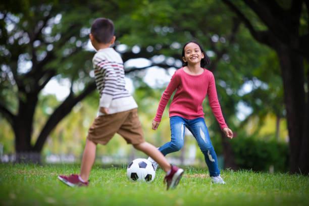 Asia Chico y chica que disfruta con el juego de futbol en el exterior - foto de stock