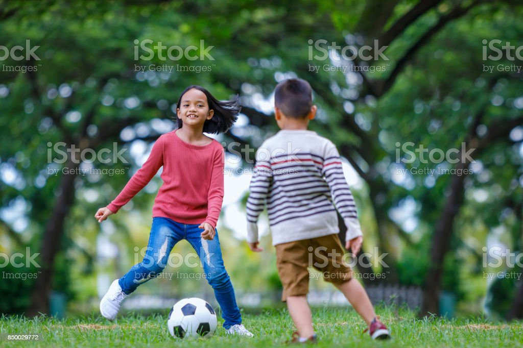 asian boy and girl enjoying with soccer game at outdoor stock photo