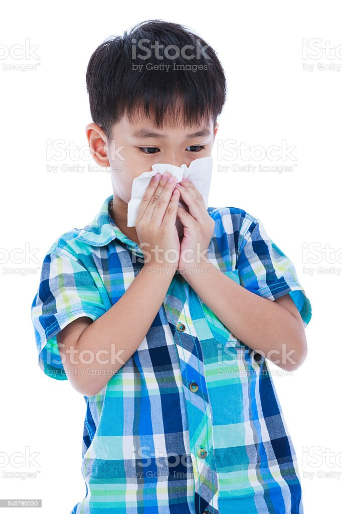 Asian boy blowing his nose into tissueon. Isolated on white. - foto de acervo