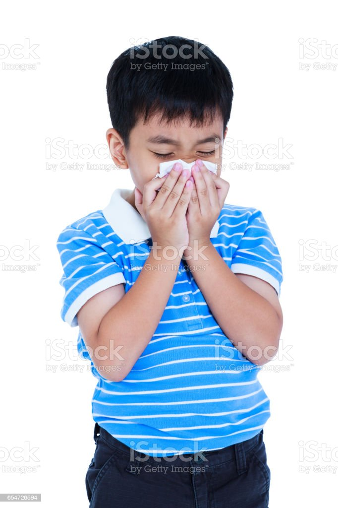 Asian boy blowing his nose into tissueon. Isolated on white. stock photo